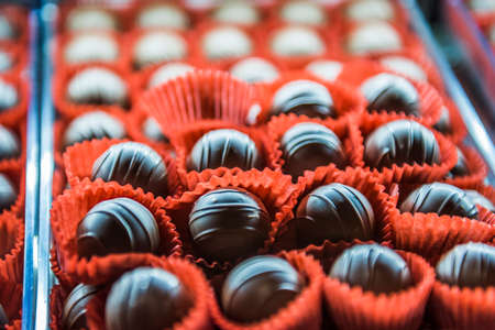 ribbed: Ribbed chocolate truffles in red muffin paper liner cups on a tray Stock Photo