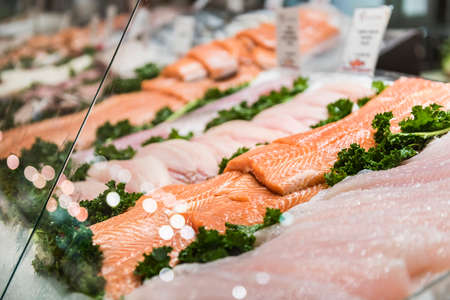 filets: Seafood stand with cuts and filets of salmon and tuna on ice behind glass