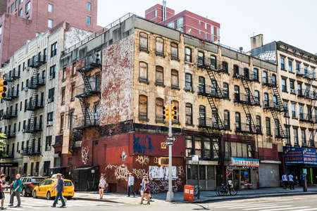 apartment shortage: New York, USA - June 18, 2016: People walk next to old, rusty building with graffiti in Chinatown in New York City Editorial