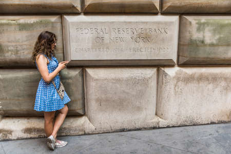 federal reserve: New York, USA - June 18, 2016: Federal Reserve Bank of New York sign with young woman on mobile phone