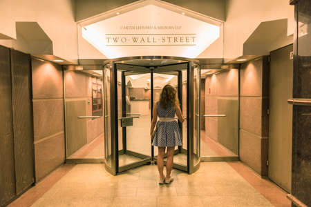 financial market: New York, USA - June 18, 2016: Young woman entering two wall street building with office of Carter Ledyard & Milburn LLP