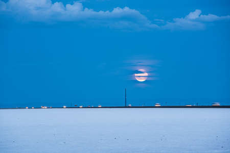 rises: Bonneville White Salt Flats with highway and cars, while pink supermoon rises
