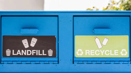 landfill: A blue trash container with two openings, landfill or recycle