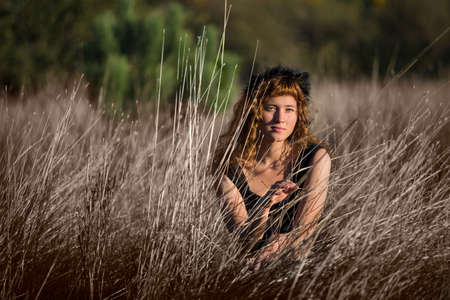 ginger hair: Young female in tall dry hay grass in black dress and ginger hair Stock Photo