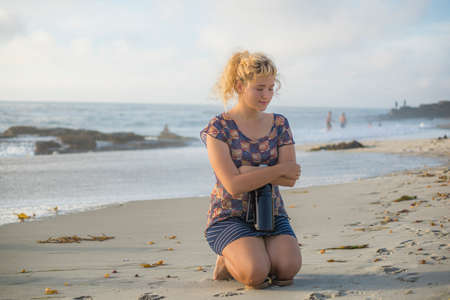 shivering: Cold shivering Young blonde woman sitting holding flask on beach in California with eyes closed