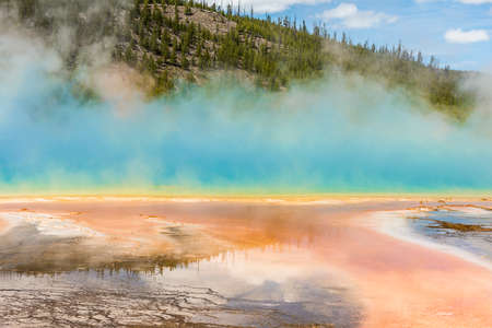 hydrothermal: Rising blue steam and mist from hot spring in Midway Geyser basin at Yellowstone National Park with red bacterial patterns