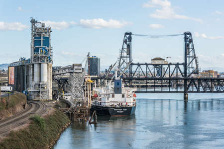 willamette: Portland, USA - March 3, 2016: Industrial view in Oregon with ship, cranes, factory and railroad by Willamette River Editorial