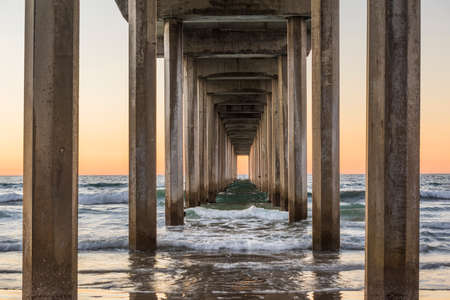 underneath: Symmetrical shot under Scripps Pier with waves during sunset in La Jolla, San Diego, California Stock Photo