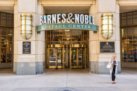 noble: Chicago, USA - May 30, 2016: Entrance to Barnes and Noble bookstore in downtown city at DePaul University center with gold detailed decoration and revolving doors, people walking