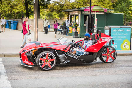 flashy: Chicago, USA - May 30, 2016: Man with cubs shirt in flashy red Polaris Slingshot Ferrari sports car on downtown street Editorial