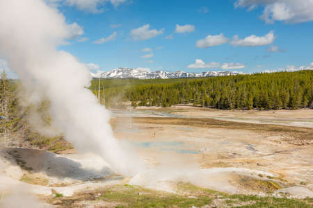 steamboat: Steamboat geyser in Norris Basin in Yellowstone National Park with hot steam, vapor, blue hot springs and mountains Stock Photo
