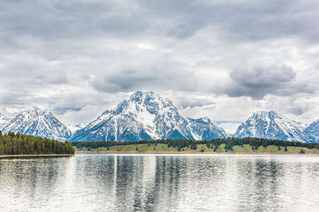 oxbow: Grand Teton mountains with lake reflection and dark storm clouds overcast in national park