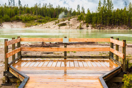 sulphuric acid: Green Sour lake in Yellowstone National Park with boardwalk sign and hot spring at Mud Volcano area