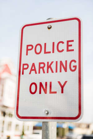 parking violation: Police parking only street sign in red
