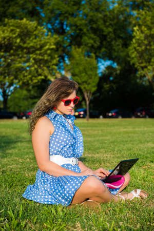 netbook: Young woman with red sunglasses and dress sitting in grass outside typing on small netbook