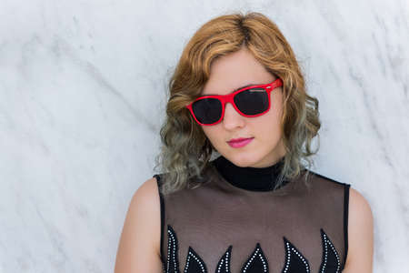 angled: Portrait of woman with red sunglasses and angled bob multicolored two-toned curly hair against marble background Stock Photo