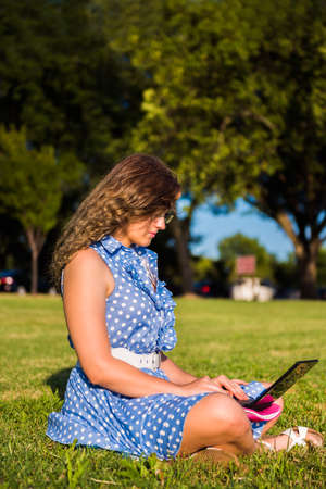 netbook: Side view of young woman in dress sitting in grass outside typing on small netbook Stock Photo