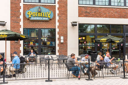 eating area: Washington DC, USA - September 24, 2016: Outside seating area of Potbelly fast food restaurant with sign and text and people eating lunch