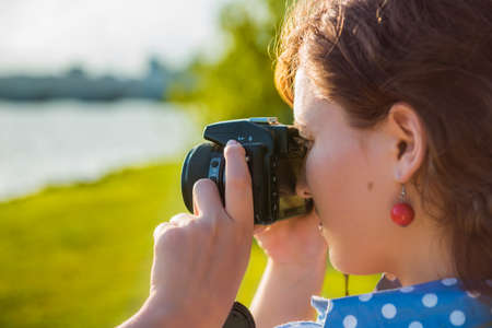 profile picture: Closeup side profile view of young woman taking a picture looking through camera outdoors in green park and river