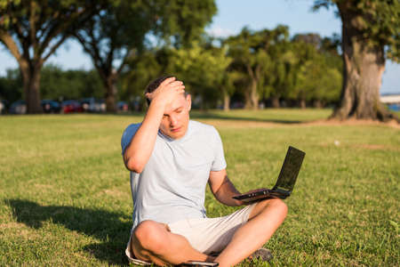 eyes looking down: Sad young man with laptop and smartphone, sitting outside in green grass in park placing hand on head due to stress headache and eyes closed looking down Stock Photo