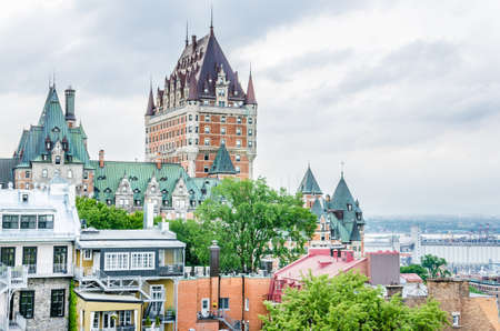 historical building: Quebec City, Canada - July 27, 2014: View of old town houses on hill with Fairmont Le Château Frontenac in downtown and Saint Lawrence river Editorial