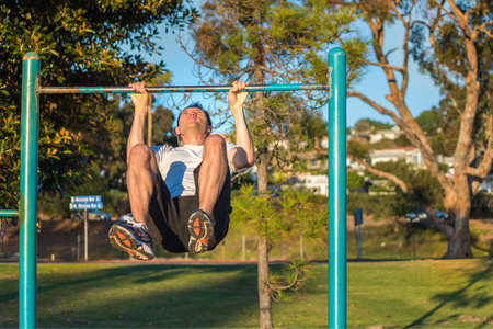strong chin: Fit muscular man doing pull ups in outdoor park