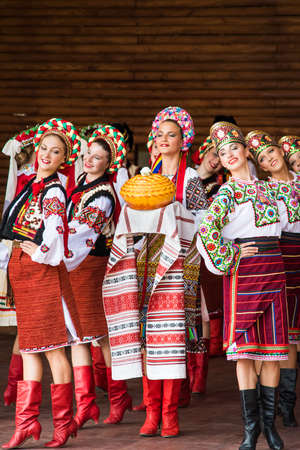 stage costume: Silver Spring, USA - September 17, 2016: Girls dressed in traditional red Ukrainian embroidered costume clothes dancing with bread at festival on stage Editorial