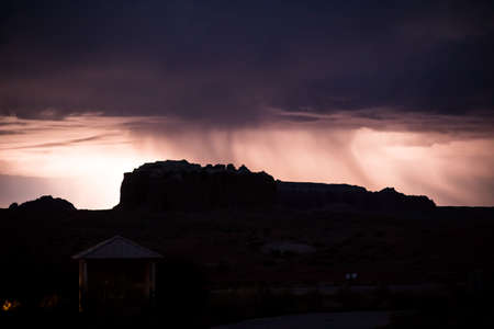 thundershower: Silhouette of canyons in Utah in front of rainy thunderstorm with lightening