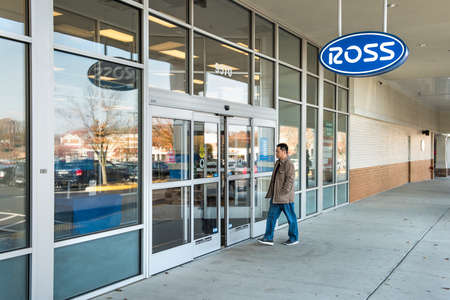 shop sign: Fairfax, USA - November 27, 2016: Ross storefront with hanging blue sign and person walking in entrance of store