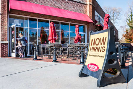 seating area: Fairfax, USA - November 27, 2016: Noodles & Company World Kitchen outdoor seating area with Now Hiring sign
