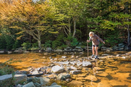 allegheny: Young woman with stick crossing Red Creek river in Dolly Sods, West Virginia Stock Photo