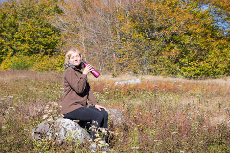 allegheny: Young woman sitting on rock in meadow drinking water from bottle and smiling