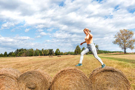 hayrick: Young woman jumping over hay roll bales in a field