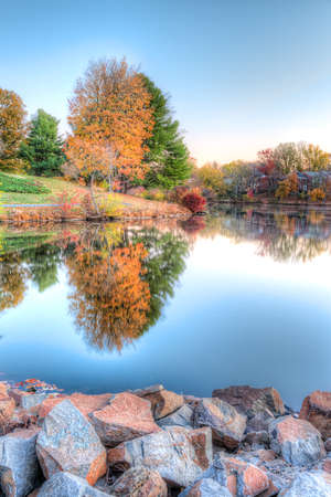 townhomes: Sunrise on Braddock lake in Burke, Virginia, USA with vertical reflection in autumn and orange tree Stock Photo
