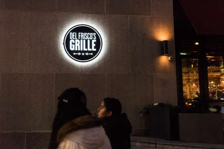 frisco: Washington DC, USA - December 29, 2016: Del Frisco grille sign by restaurant on Pennsylvania avenue  with people walking