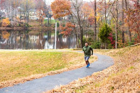 residential neighborhood: Fairfax, USA - November 24, 2016: Man jogging on trail path by lake Woodglen in Virginia near residential neighborhood