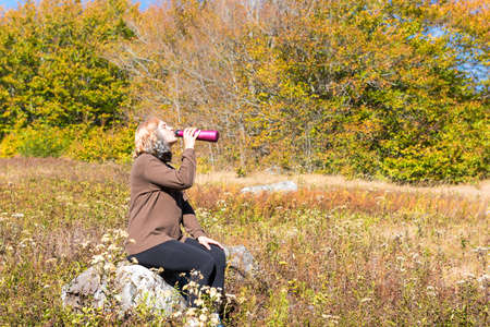 allegheny: Young woman sitting on rock in meadow drinking water from bottle during hike