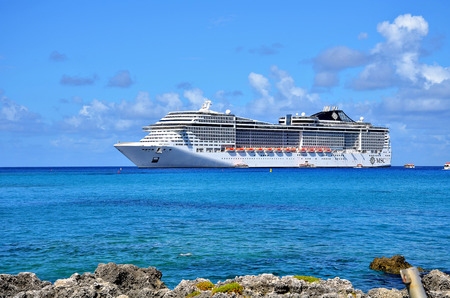 Georgetown, Grand Cayman - September 19, 2017: Transatlantico MSC Divina anchored in the clear and turquoise waters of the Caribbean Sea. Every year the city receives thousands of tourist.