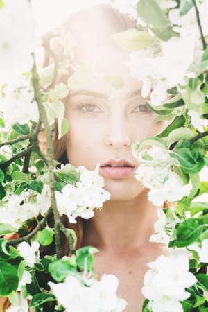 Portrait of beautiful romantic lady in a wreath of apple trees in the summer garden Banco de Imagens