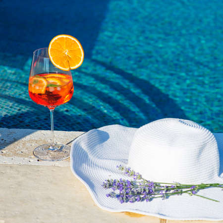 Closeup image of white hat and cocktail near swimming pool, summer vacation concept