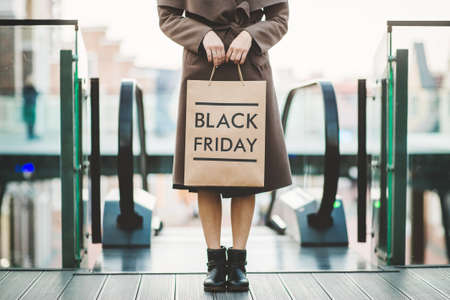 Beautiful elagance woman holding Black Friday paper bag in shopping mall Stockfoto