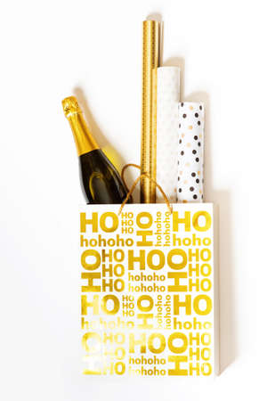 consumerism: Shopping bag with wrapping paper and bottle of champagne Stock Photo