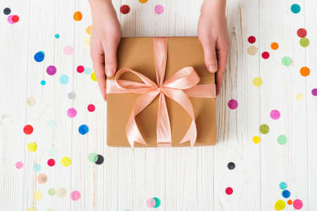 Man hands holding present box with pink bow on white wooden background with multicolored confetti. Flat lay style. Stock Photo