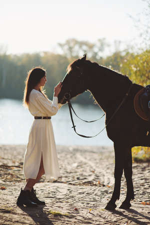 Beautiful pensive woman stroking horse standing near the river Stok Fotoğraf