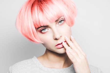 Belle fille aux cheveux toniques de couleur corail vivant.