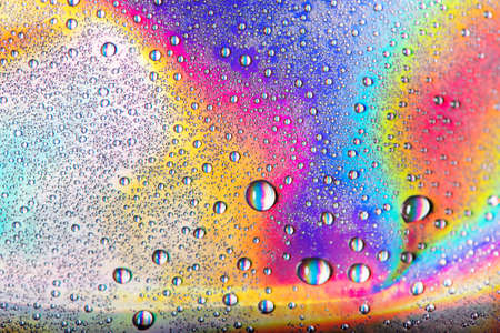 Drops of water on vibrant holographic neon background. Macro shot