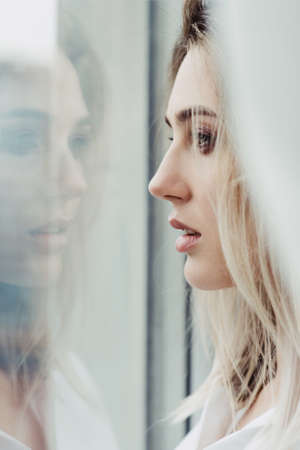 Beautiful woman looking out of the window in which her face is reflecting Stock Photo