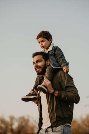 Father giving son ride on his shoulders during walking in autumn park. Stok Fotoğraf