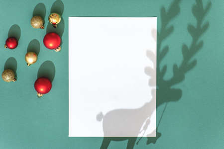Festive composition with Christmas decoration, blank sheet of paper and shadow of deer on green background. Stock Photo