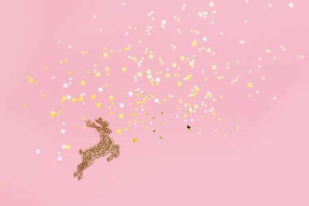Wooden deer decoration on pink background with little golden stars.